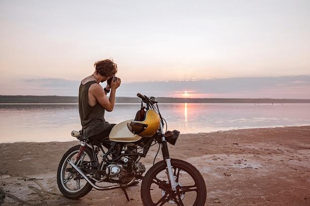 Giovane che fa foto con la fotocamera mentre è seduto sulla sua motocicletta all'aperto