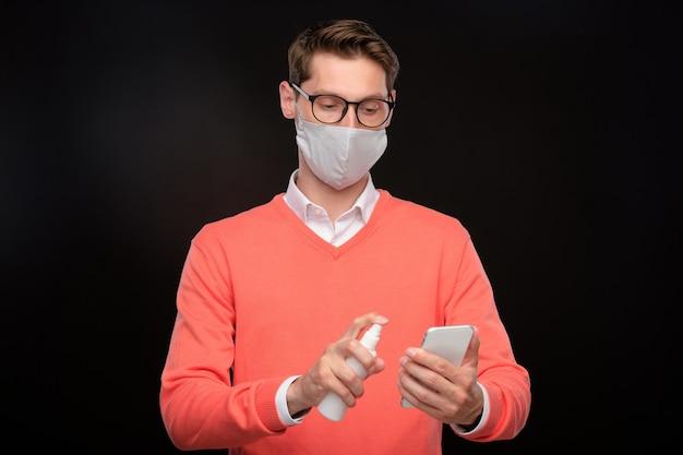 Giovane in maschera e occhiali che disinfettano smartphone con disinfettante su sfondo nero, concetto di coronavirus
