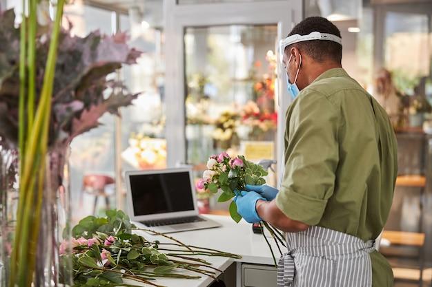 Il giovane in maschera e guanti sta lavorando in un negozio di fiori durante la quarantena e sta usando il laptop per comunicare con i clienti