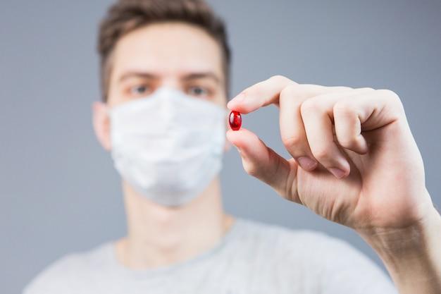 Giovane in una maschera con una pillola rossa in mano