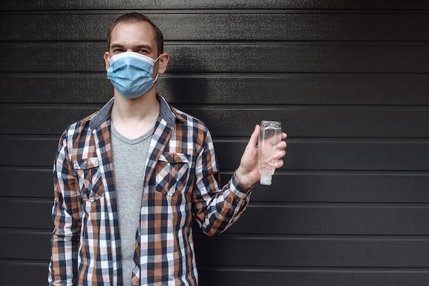 Giovane uomo in una maschera medica tenendo la bottiglia con un disinfettante antibatterico liquido