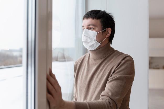 Un giovane uomo con una mascherina medica guarda fuori dalla finestra. solitudine in isolamento. pandemia di coronavirus.