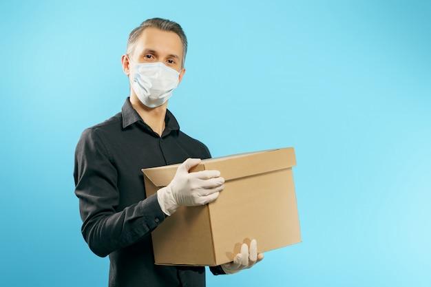 Giovane in una mascherina protettiva medica e guanti che tengono una scatola su un fondo blu. consegna sicura