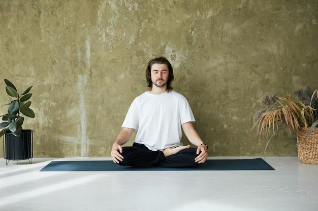 Giovane uomo in meditazione posa a casa, bel maschio seduto in lotus sul materassino yoga con piante, copia dello spazio
