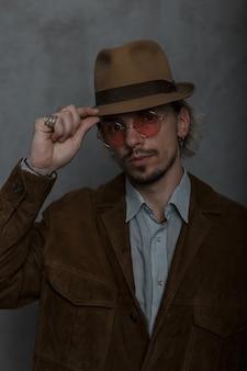 Modello di giovane uomo in abiti eleganti in stile retrò in occhiali vintage in un cappello vecchio stile in posa in studio vicino a un muro grigio. bel ragazzo elegante barbuto. ritratto.