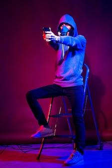 Modello di giovane uomo in posa in uno studio in una luce al neon alla moda in una tuta sportiva, cappuccio e maschera che tiene la pistola.