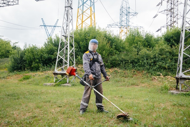 Un giovane che falcia l'erba sul territorio di una sottostazione elettrica in tuta. pulizia dell'erba presso l'azienda, implementazione di misure di sicurezza antincendio.