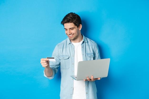Giovane uomo ordina online, tenendo carta di credito e laptop, acquisti in internet, in piedi contro il muro blu
