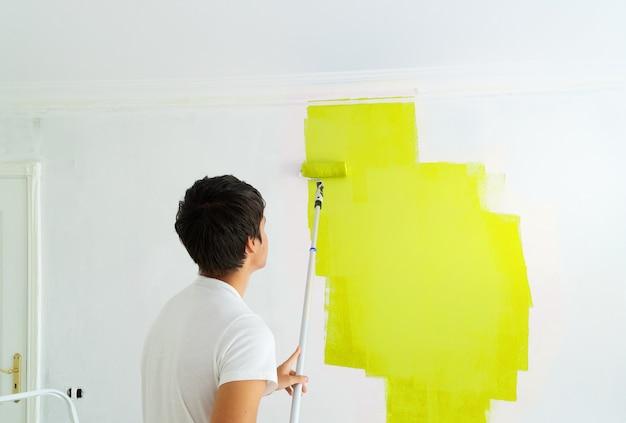 Giovane uomo pittura parete illuminante di colore giallo nella stanza intonacata bianca