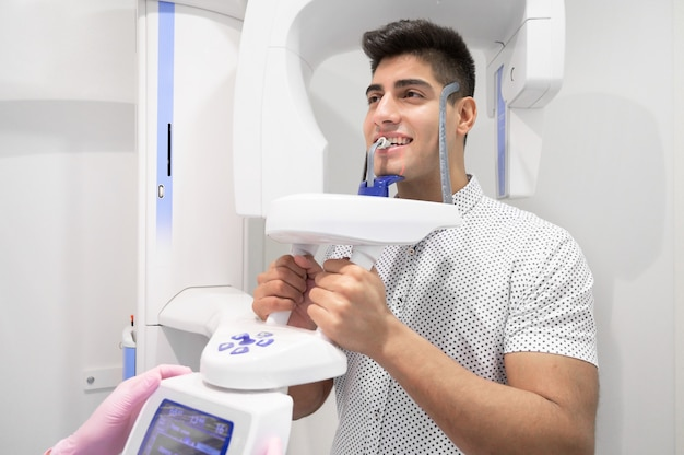 Paziente del giovane che sta nella radiografia panoramica della macchina dei raggi x
