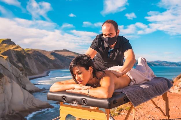 Un giovane che esegue un massaggio nella natura sulla costa vicino al mare, un sogno che si avvera, massaggiatrice con maschera facciale nella pandemia di coronavirus