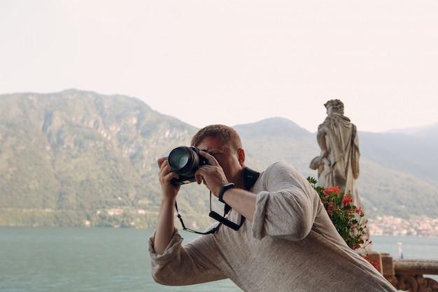 Il fotografo del giovane fotografa con una macchina fotografica professionale, le montagne e un lago. concetto di viaggio fotografico.