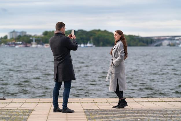 Giovane che fotografa la sua ragazza o moglie su un lungomare ventoso in una fredda giornata autunnale utilizzando il suo telefono cellulare