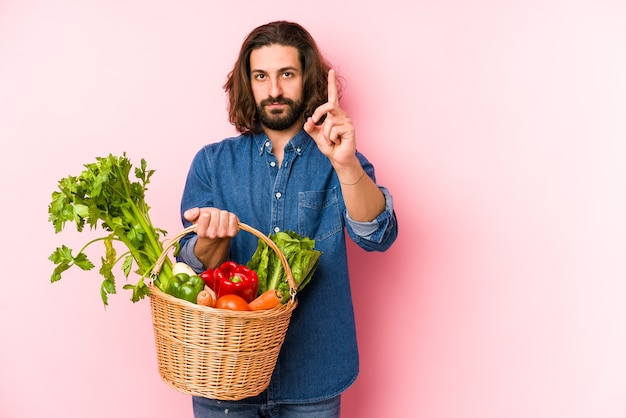 Giovane che raccoglie verdure biologiche dal suo giardino isolato che mostra il numero uno con il dito.