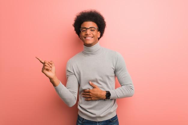 Giovane uomo sopra un muro rosa che punta verso il lato con un dito