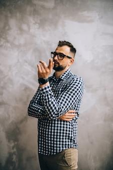 Un giovane uomo con una camicia a quadri e occhiali posa per la fotocamera