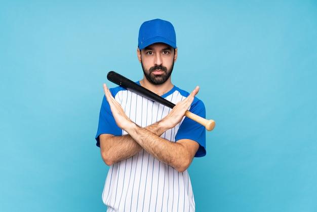 Giovane che gioca a baseball sopra la parete blu isolata che non fa gesto