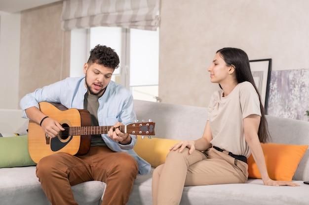 Giovane che suona la chitarra e canta davanti a sua moglie in soggiorno