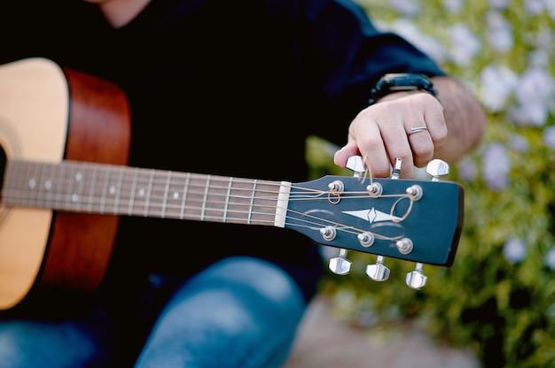 Un giovane uomo che suona una chitarra mentre era seduto in un giardino naturale