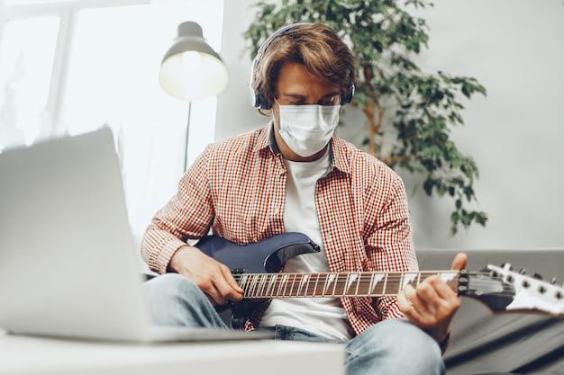 Il giovane suona la chitarra a casa nella mascherina medica