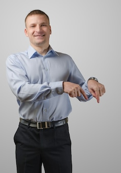 Il giovane punta la mano verso qualcosa. isolato sulla superficie bianca