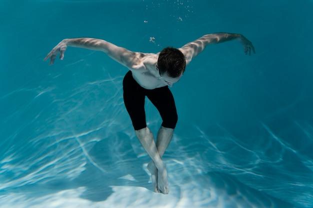 Giovane uomo in posa sommerso sott'acqua