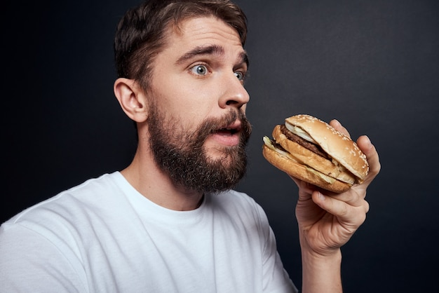 Giovane che propone con un hamburger