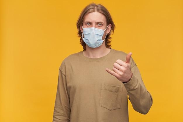Giovane, ragazzo positivo con capelli biondi, barba e baffi. indossare un maglione beige e una maschera protettiva medica. mostrando il segno di shaka. isolato su muro giallo