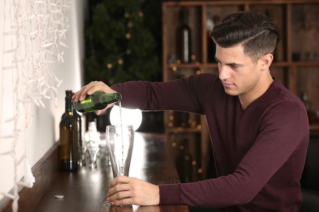 Giovane che versa birra in vetro al bar. problema di alcolismo