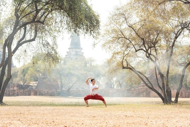 Giovane che pratica una danza tradizionale thailandese
