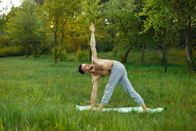 Giovane uomo a praticare yoga all'aperto