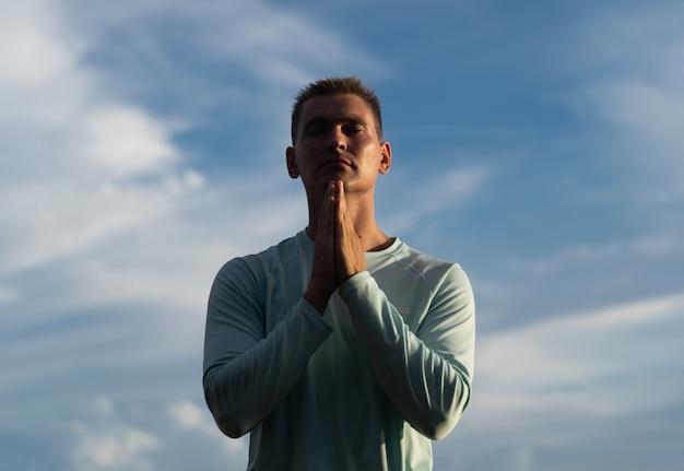 Il giovane prega sul fondo del cielo blu. pentimento, rimpianto e concetto di speranza.
