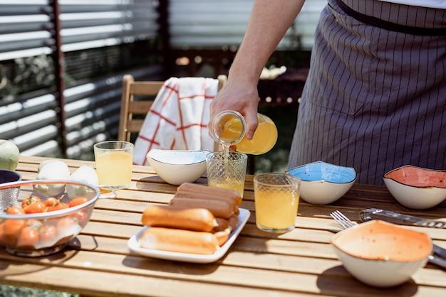 Giovane uomo che prepara tavolo per picnic, tenendo in mano una bottiglia con limonata nel soleggiato pomeriggio estivo. barbecue in giardino Foto Premium