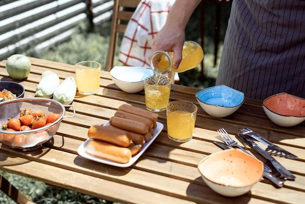 Giovane uomo che prepara tavolo per picnic, tenendo in mano una bottiglia con limonata nel soleggiato pomeriggio estivo. barbecue in giardino