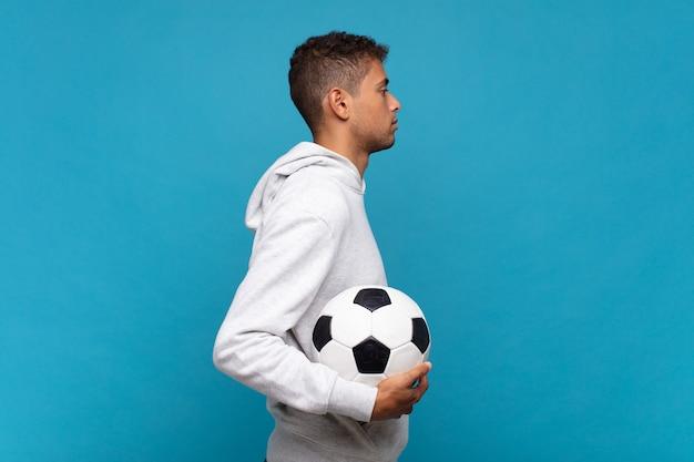 Giovane uomo in vista di profilo che cerca di copiare lo spazio davanti, pensare, immaginare o sognare ad occhi aperti. concetto di calcio