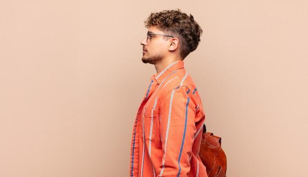 Giovane uomo in vista di profilo che cerca di copiare lo spazio davanti, pensare, immaginare o sognare ad occhi aperti. concetto di studente