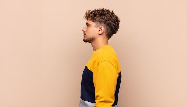 Giovane uomo in vista di profilo che cerca di copiare lo spazio davanti, pensare, immaginare o sognare ad occhi aperti