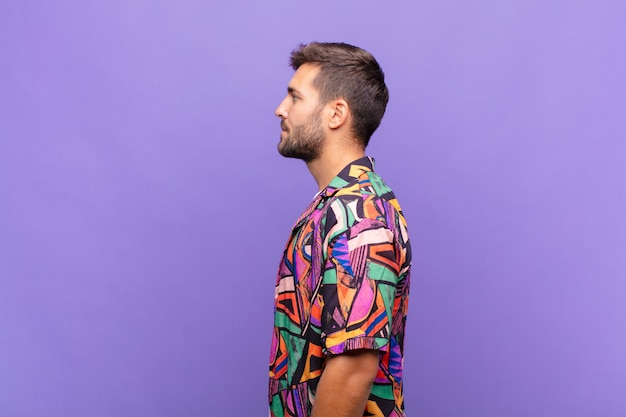 Giovane uomo sulla vista di profilo che cerca di copiare lo spazio davanti, pensare, immaginare o sognare ad occhi aperti