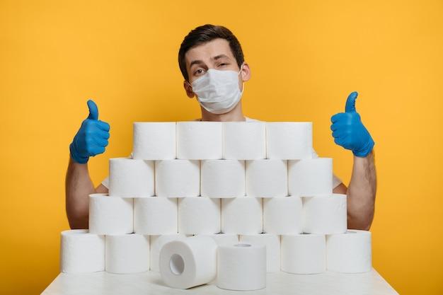 Giovane con maschera protettiva e guanti medici dietro la pila di carta igienica