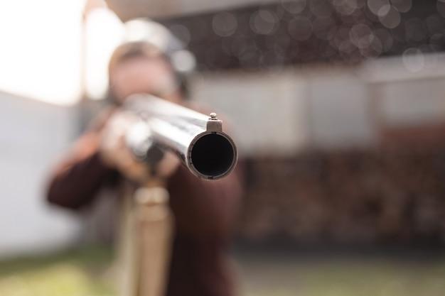 Un giovane in occhiali protettivi e cuffie. un fucile a pompa.