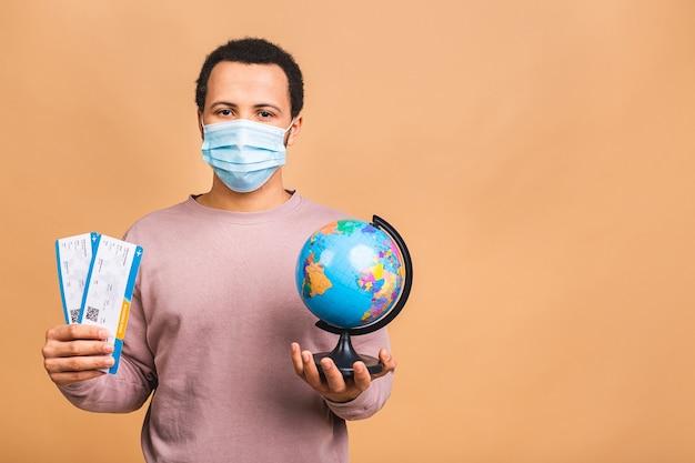 Giovane uomo in maschera protettiva holding biglietti della carta d'imbarco e globo isolato su beige
