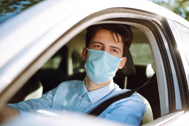 Giovane uomo in una maschera protettiva seduto in macchina