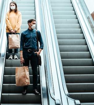 Giovane uomo in una maschera protettiva in piedi su una scala mobile in un centro commerciale. coronavirus in città