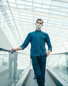 Giovane uomo in una maschera protettiva in piedi sui gradini della scala mobile