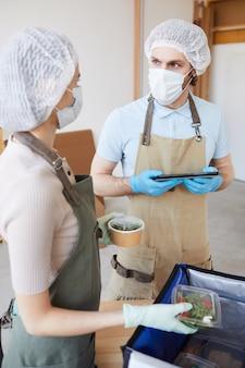 Giovane uomo in maschera protettiva utilizzando la tavoletta digitale e parlando con il suo collega mentre imballano il cibo per la consegna
