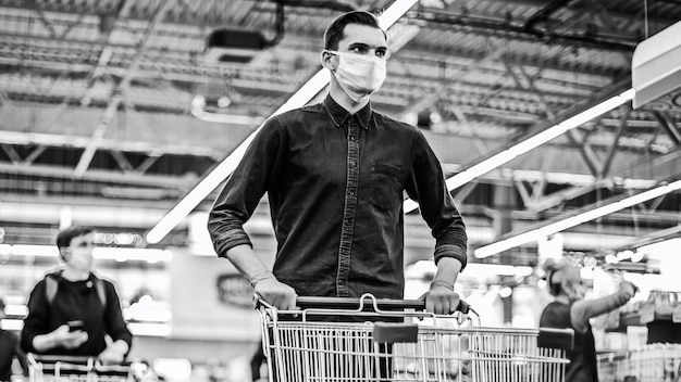 Giovane uomo in una maschera protettiva con un carrello della spesa