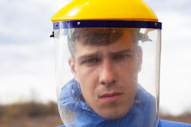 Giovane in primo piano protettivo di plastica medico della maschera che sta sulla via.