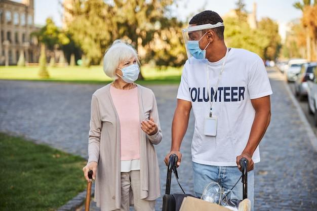 Giovane con scudo protettivo che spinge una sedia a rotelle e guarda la donna anziana con un bastone da passeggio al suo fianco all'aperto