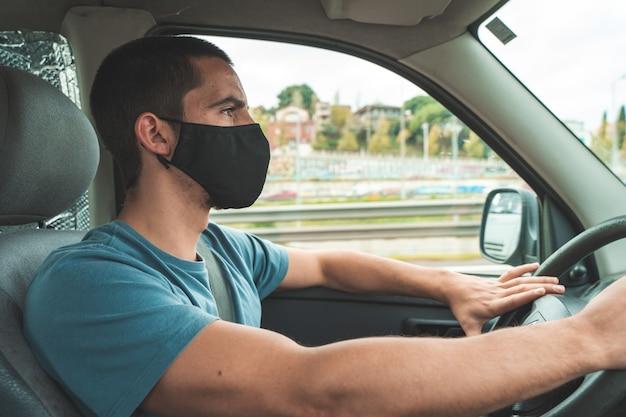 Giovane uomo in maschera medica sterile protettiva che guida l'auto concetto di coronavirus