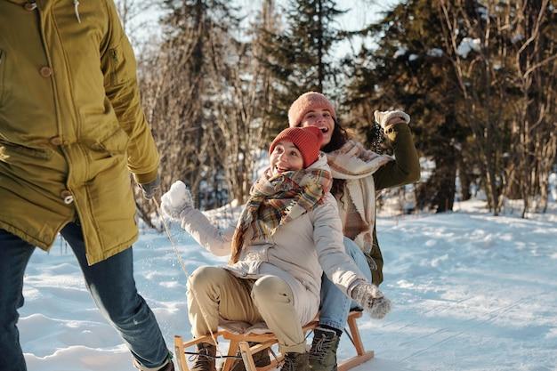 Giovane che tira la slitta con due ragazze felici
